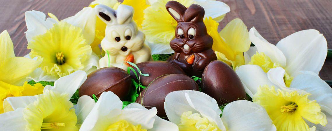 Schokoladenosterhasen, umgeben von Schokoladeneiern für Kinder