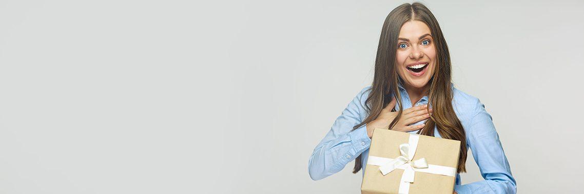 Glücklicher Damenchef, der eine Geschenkbox hält.